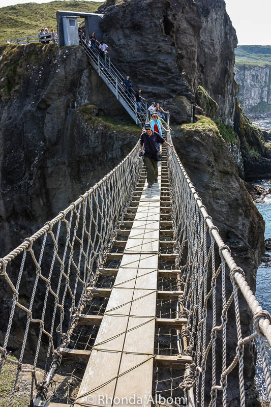 Walking across Carrick A Rede Rope Bridge in Northern Ireland. Often called the Giant's Causeway bridge, it is one of the most famous bridges in Ireland