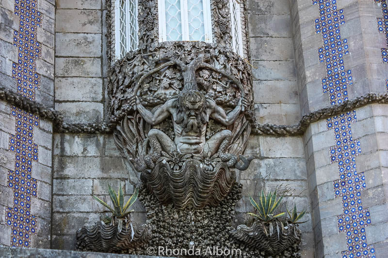 Holding up one of Pena Palace's window is this mythological triton in Sintra Portugal
