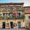 Santillana Del Mar, rustic stone buildings dripping with colourful balcony flowers.