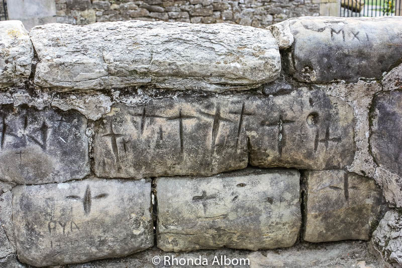 Crosses carved into the stones on a wall near the Church of the Colegiata in Santillana Del Mar, Spain
