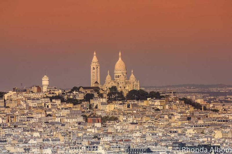 Avoid crowds in Paris by visit sites early in the morning, like Sacre Coeur in the distance in Paris France