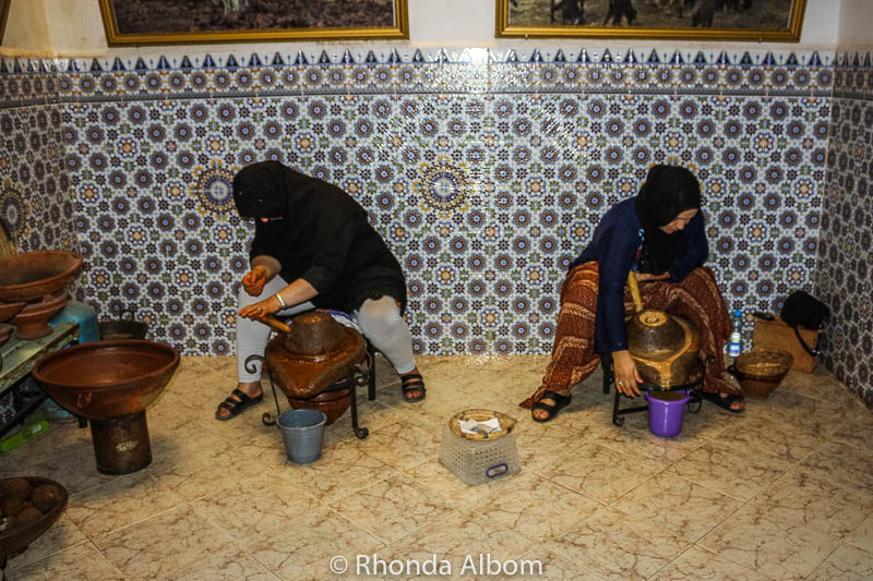 Berber women hand grinding the seeds to make argon oil in the Medina in Taroudant, Morocco