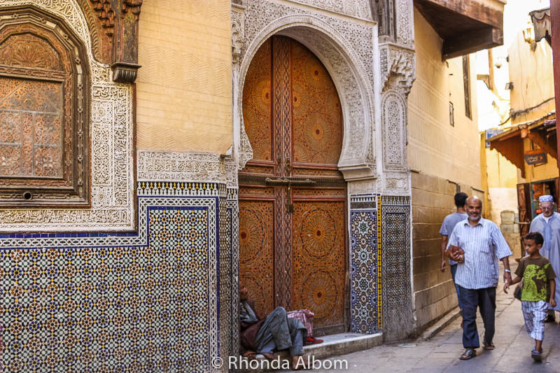 Wooden Moroccan doors set in beautifully tiled arched doors