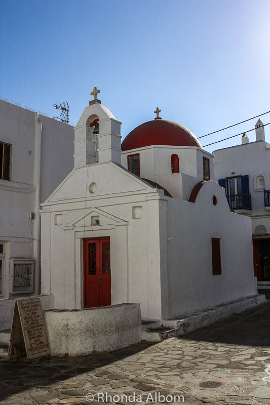 A classic red roofed chapel on a Greek island