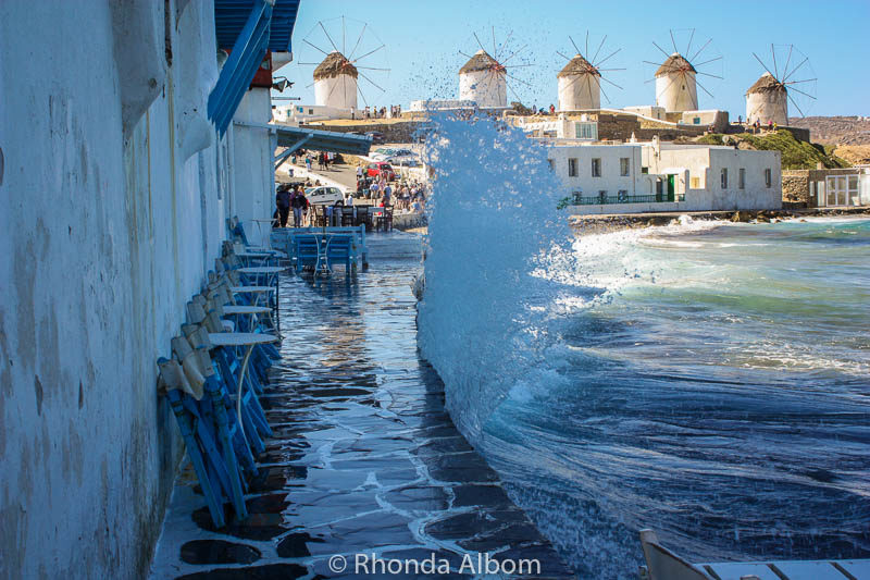 A wave of water rises up along the coast while five  of the Mykonos windmills stand in the background.