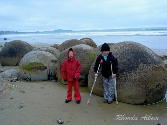 Girls standing in front of Alien Egg? At Moeraki Boulders in New Zealand's South Island