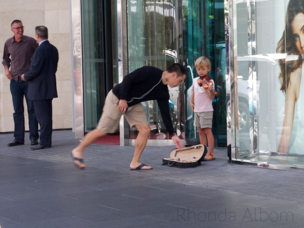 Child playing violin on Auckland Street, New Zealand
