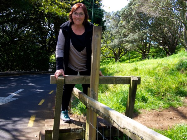 Climbing a stile to go enter a dirt path in Auckland New Zealand