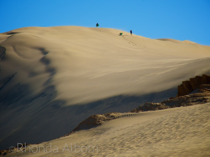 Our girls and their friend walking up the sand dunes as the wind blows.