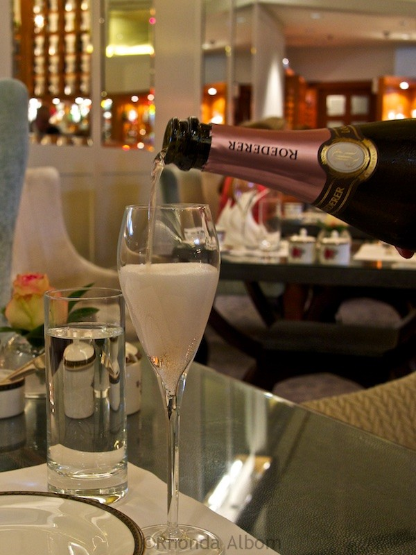 Pouring a glass of Louis Roederer Rose Champagne at Afternoon Tea at Palm Court in the Langham Hotel, Auckland New Zealand