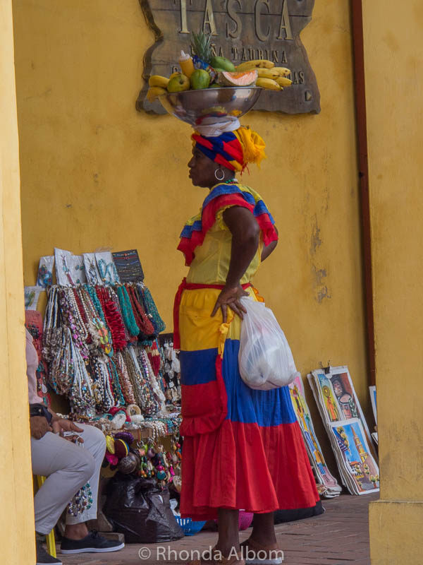 Woman carrying a fruit basket on her head.