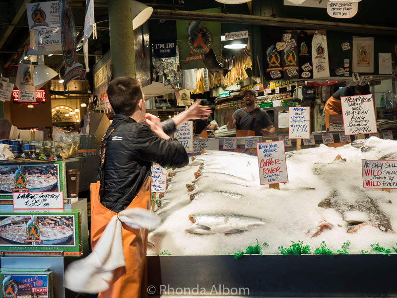 A fishmonger catching fish at the Pike Place Fish Market in Seattle Washington