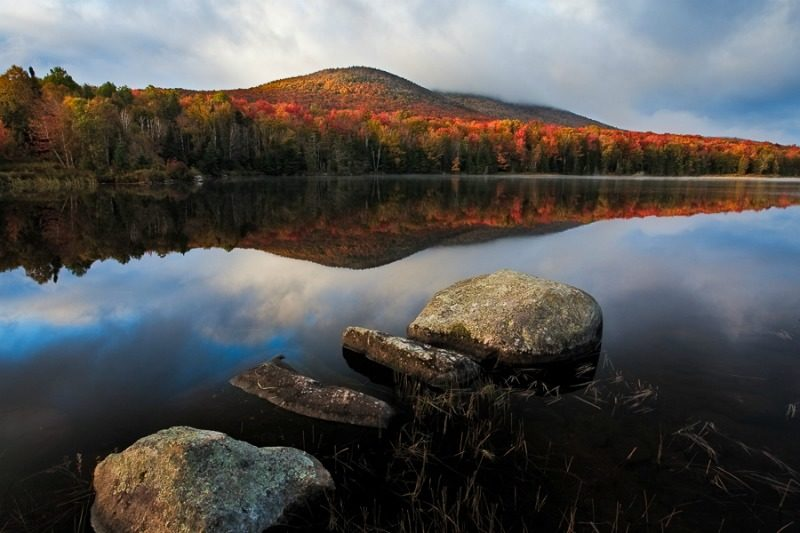 Colorful and reflective New England fall foliage. This photo from Vermont USA