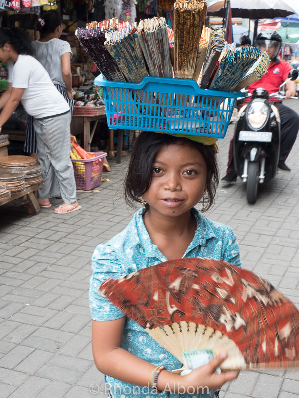 Girl selling fans in a market in Ubud, Bali