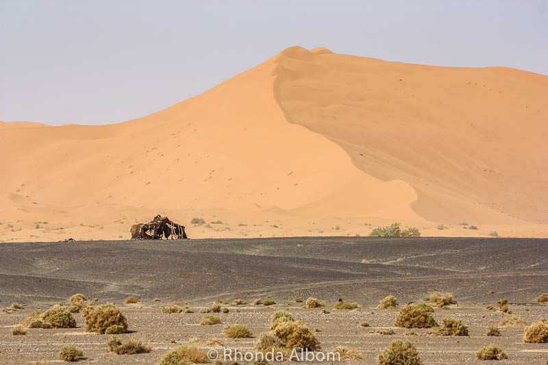 A Bedouin structure in the distance, at the base of the sand dunes in the Sahara desert in Morocco