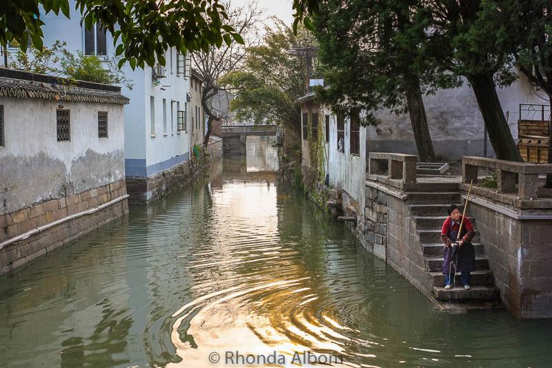 Woman washing her mop in a canal in the Pingjiang Historic Quarter of Suzhou China