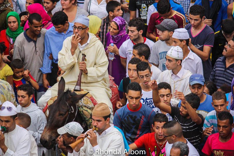 Musician pauses for a smoke during the Moussem of Moulay Idriss II in Fes Morocco