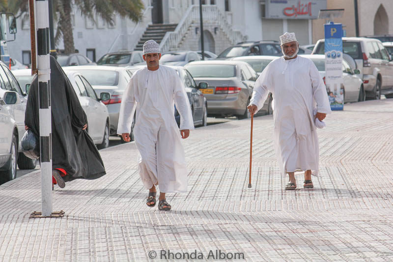Two men in traditional dress walking along the corniche in Muscat Oman