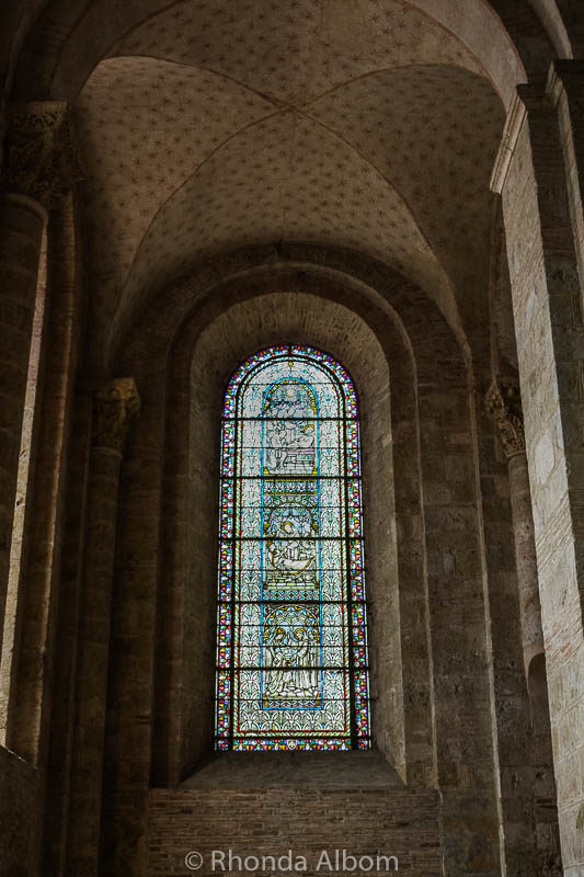 Colourful stained glass windows and Romanesque arches in the Basilica of St Sernin in Toulouse France