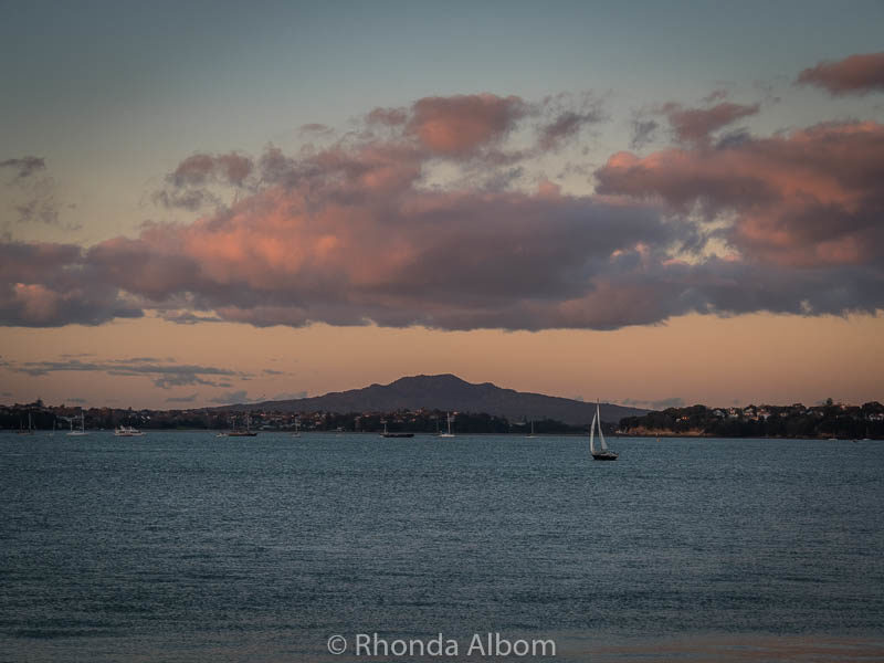 A yacht sails by Rangitoto Island as sunset approaches in New Zealand