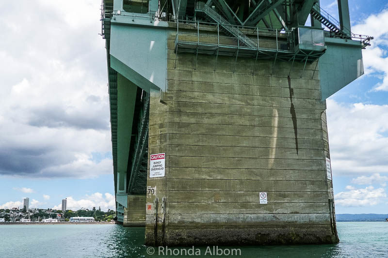 Caution, Bungy Jumping Overhead sign under the Harbour Bridge. It is one of the fun things to do in Auckland New Zealand