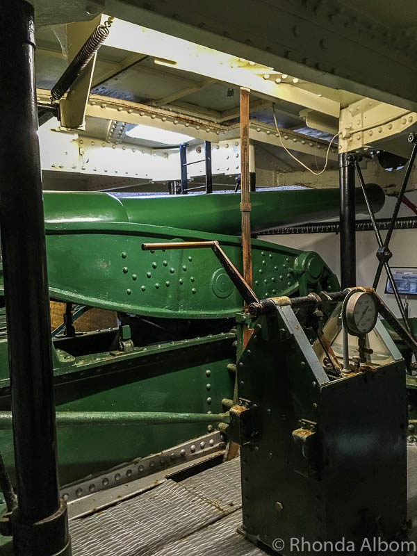The Armstrong disappearing gun with its hand driven pump in the foreground at Fort Taiaroa in Dunedin New Zealand