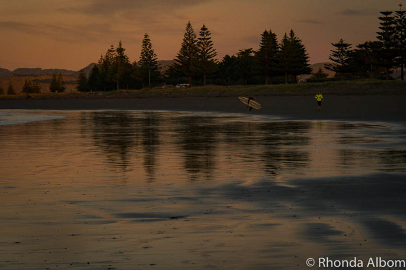 Surfers heading out at sunrise in Gisborne New Zealand