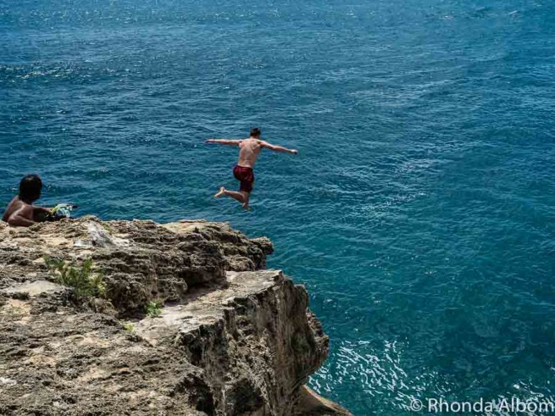 Leaping off the cliff at Shipwreck Point on Kauai Hawaii