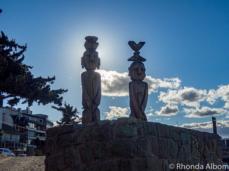 Native wood carvings of two people in front of the Nahuel Huapi Iglesia Cathedral in San Carlos de Bariloche, Argentina.