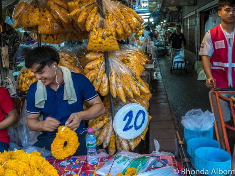 Workers create marigold rings in the Flower Market