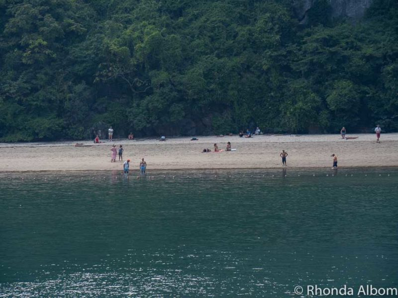 People relaxing or swimming at a beach on one of the Halong Bay islands