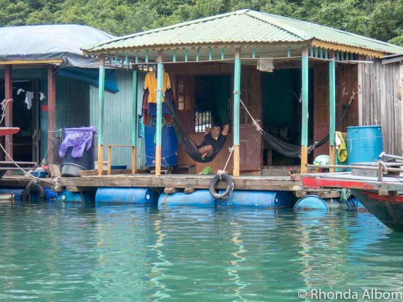 Man relaxes in a hammock in a fishing village in Vietnam