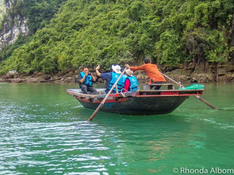 Bamboo boat maneuvered through a fishing village