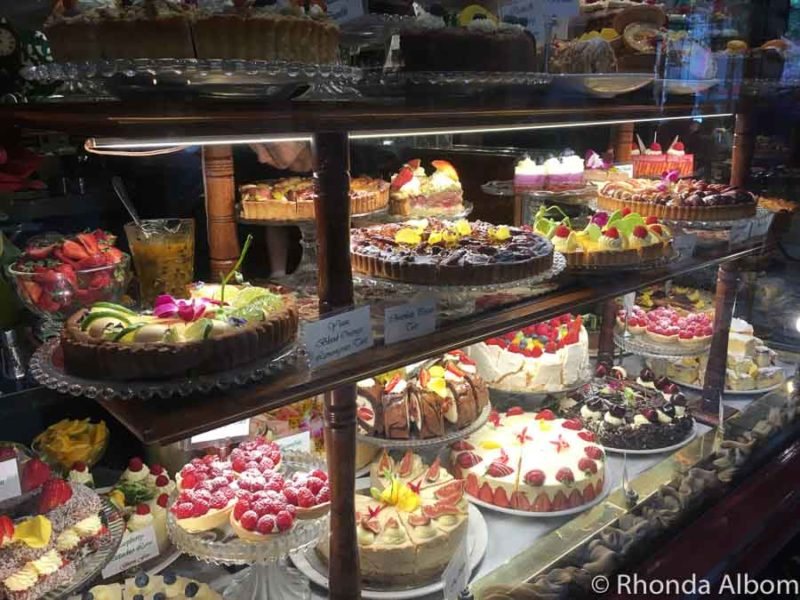 Three shelves of cakes and other sweet desserts in the display case at Hopetoun Tea Rooms, part of the Melbourne cafe culture