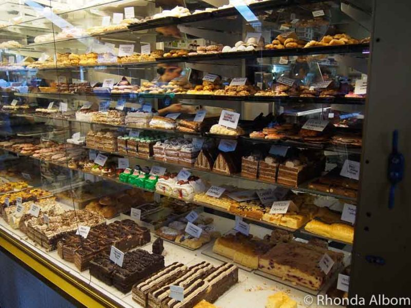 Looking at the cakes displayed in a shop in the St Kilda neighbourhood which is filled with some of the best cafes in Melbourne Australia