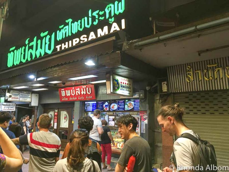 A long queue of people wait outside Thipsamai Restaurant in Bangkok Thailand for Pad Thai