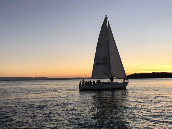 Yacht sailing during sunset, one of the best things to do in Auckland at night. Photo courtesy of Explore Group