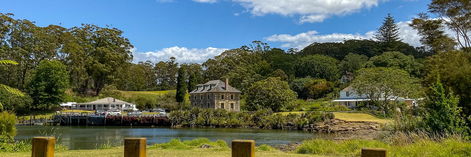 Kerikeri mission station seen from across the Kerikeri river. View includes the green grass on both sides, the blue river, the old stone store and the kemp house and the trees behind the buildings.