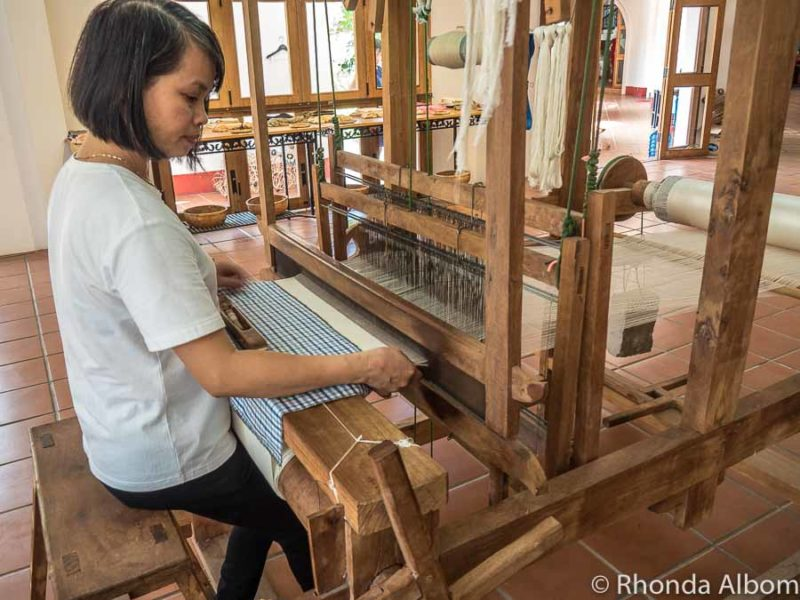 Women demonstrates the silk weaving machines at Yaly Couture one of the Hoi An attractions