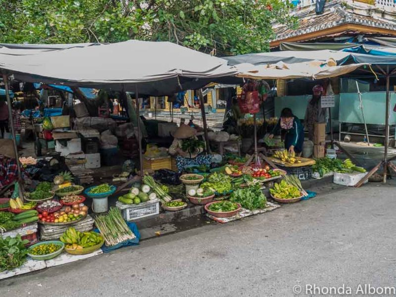 Fruit and vegetables are some of the best food in Hoi An sold at stalls along the road just outside the central market]