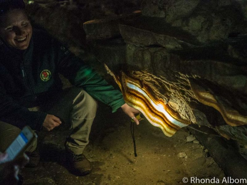 Guide lights up a curtain of calcite that looks like a giant strip of bacon