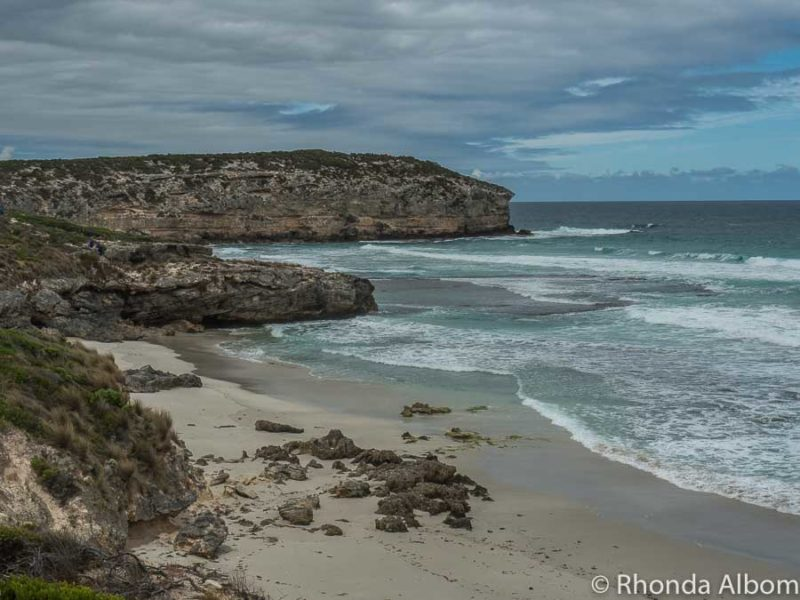 Ocean waves coming into along a sandy beach and along the cliffs in Australia
