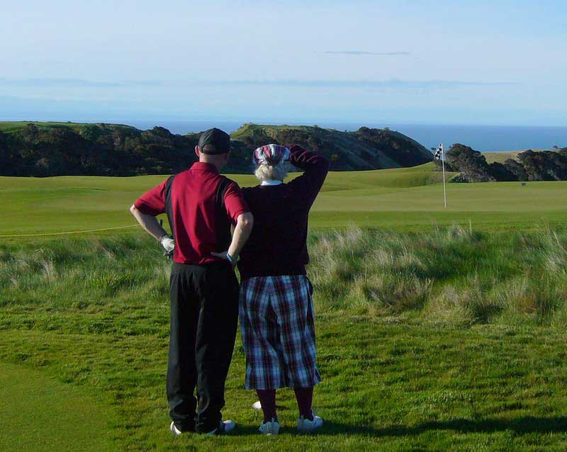 Two golfers look out across the Cape Kidnappers Golf Course, one of the top things to do in Hawkes Bay