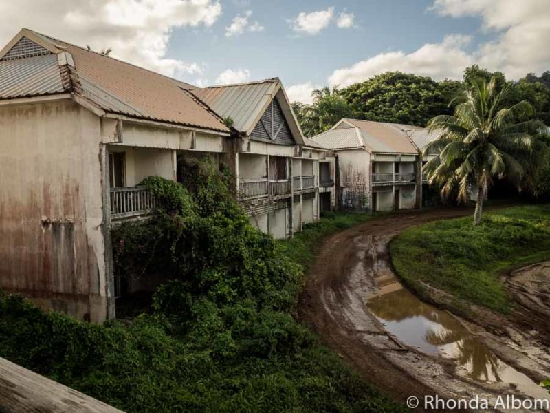 Wet and muddy road passing in front of several derelict buildings of the abandoned Sheraton resort complex in the Cook Islands