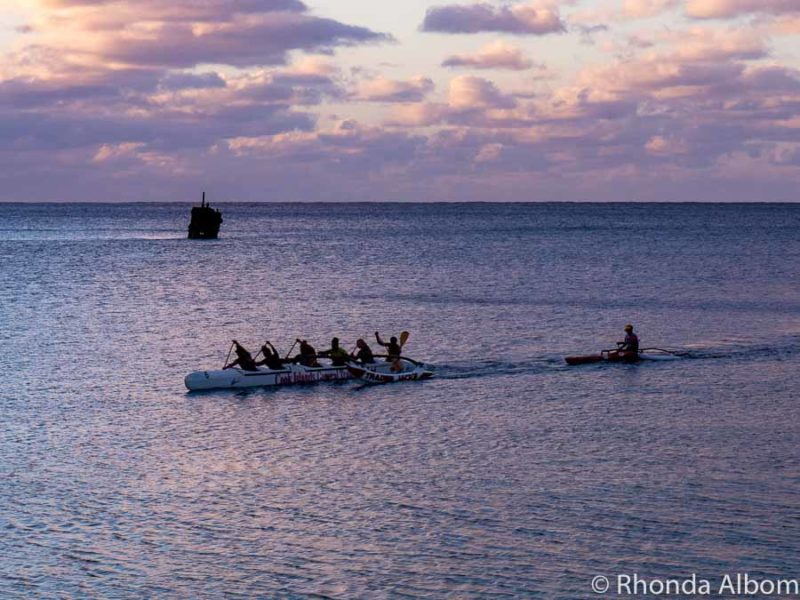 The wreck of the Matai sits in the background as an outrigger canoe sails by seen from Trader Jacks Restaurants, Rarotonga, Cook Islands