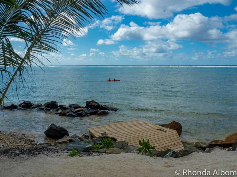 Sand, small boardwalk, and a rocky shore at a resort on Rarotonga in the Cook Islands