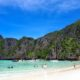 Swimmers enjoying the crystal clear waters and white sand of Maya Bay in Thailand