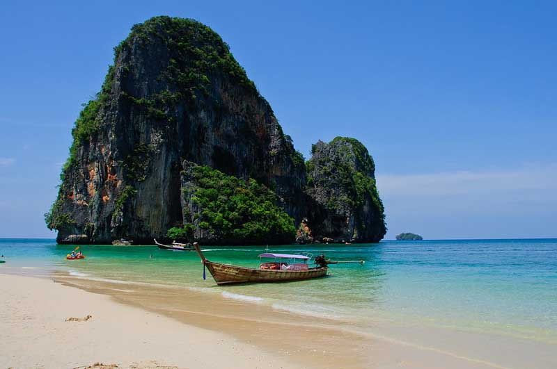 Kayak at the shore in front of a huge rock outcropping on Phra Nang one of the best beaches in Thailand