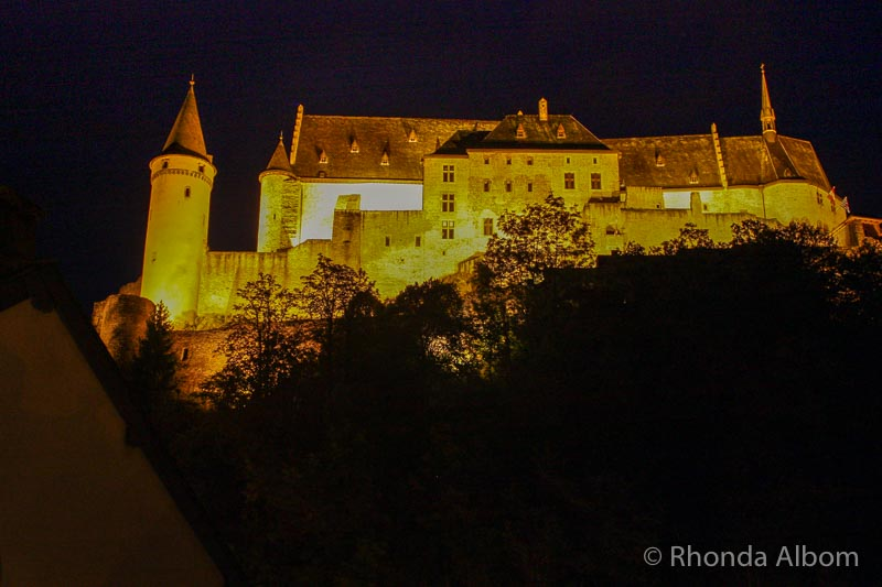 Golden light on a castle on a hill against the black night sky and seen from one of the many hotel alternatives in Luxembourg