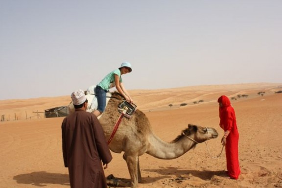riding a camel in Oman
